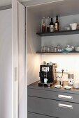 Offene Schiebetür und Blick auf Küchenschrank mit Espressomaschine