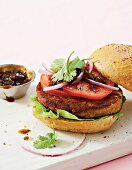 A bobotie & lentil burger with tomato and onion