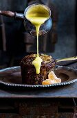 Lemon and vanilla sauce being poured over malva pudding