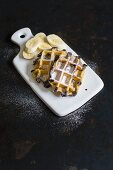 Croissant and chocolate waffles with banana on a white ceramic board