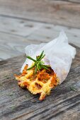 A piece of rosemary and potato waffle in greaseproof paper