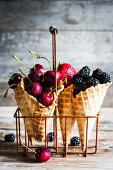 Fresh cherries, strawberries and blackberries in ice cream cones