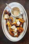 Grilled chicken wings marinated in yoghurt and curry with a yoghurt and coriander dip