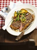 Pan-fried ox sirloin steak with herb butter and green beans with bacon