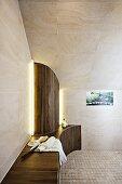 Designer-Bad mit Sitzfläche und halbrunder Verkleidung unter gefliester Dachschräge