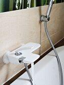 weiße Badewannenarmatur und Duschschlauch an Fliesenwand