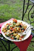 Smashed potatoes with black olives and tomatoes