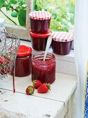 Strawberry jam with vanilla in glass jars on a window sill