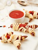 Pastry wrapped sausages with ketchup as Halloween mummies