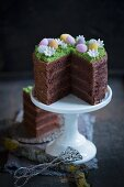 An Easter cake decorated with a chocolate glaze and sugar eggs, sliced