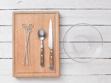 Kitchen utensils: metal skewers, cutlery and a glass bowl