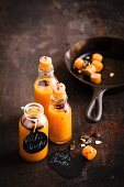 Vegan pumpkin shots with chilli flakes in small glass bottles