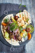 Kofte kebabs with houmous and tomato salad on pitta breads