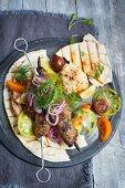 Köfte-Spieß mit Hummus und Tomatensalat auf Pitabrot