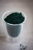 Spirulina powder in a glass cup