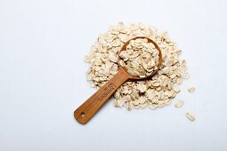 A pile of oats with a wooden spoon on a white surface