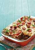 Classic lasagne in a casserole dish with one slice removed