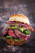 A mini burger with roast beef, jalapenos, spinach and bean sprouts