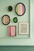 Verschiedene Bilderrahmen mit Biedermeierstoffen an pastellgrüner Wand mit Zierleisten