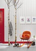 Birkenstämme als Garderobe neben orangefarbenem Retro-Schaukelstuhl vor Tapete mit schimmerndem Fischgrätmuster