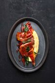 Pork escalope in sweet and sour plum sauce with ham crisps and polenta
