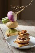 Roast slices of turnip in front of three different varieties of autumn turnip