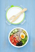 A lunchbox with Nice salad (tuna, egg, beans, olives, cucumber and tomatoes)