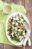 Salad with surimi, quail eggs, radishes, peas and mayonnaise dressing