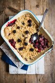 Blackberry & apple crumble in an enamel dish with a spoon (seen from above)