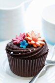 Cupcake decorated with chocolate ganache and sugar flowers