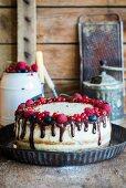 A semi-naked cake with vanilla cream, fresh berries and chocolate ganache