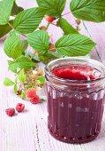 A jar of raspberry jam and fresh raspberries