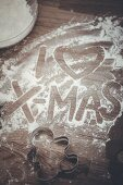 'I Love Xmas' written in flour on a wooden board