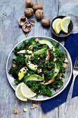 A curly kale salad with avocado, apple, walnut and black lentils