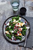 A curly kale salad with pomegranate seeds, sheep's cheese and apple slices