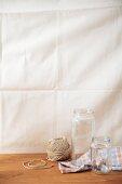 An arrangement of preserving jars, a tea towel and a reel of string
