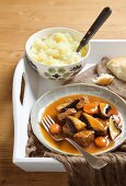 Beef stew with mushrooms and dark beer sauce served with a side of mashed potato