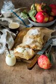 Apple strudel with cream on a wooden board
