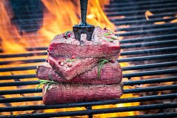 Stakes on a meat fork on a barbecue with rosemary and pepper