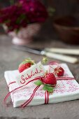 Napkins with a ribbon, strawberries and a name tag