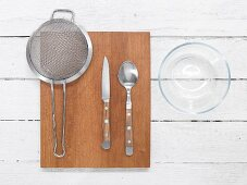 Kitchen utensils: colander, knife, spoon and glass bowl
