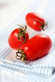 Three date tomatoes on a tea towel