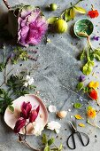 Frame of decorative flowers, florets, fruit and vegetables on stone surface