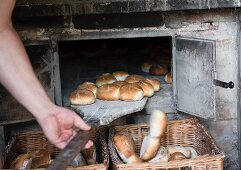 A man sliding bread rolls out of the oven and into wicker baskets