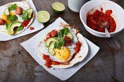 Tacos with avocado, tomato salsa, fried egg and salsiccia