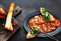 Slices of the year shank in a red pepper marinade served with crostini with veal bone marrow