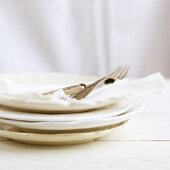 A stack of white plates with napkins and cutlery