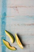 Three wedges of avocado on a wooden surface