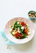A salad with spinach, apples, serrano ham, almonds and pistachios