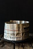 A baking tin wrapped in newspaper for a spelt and amaretto fruit cake